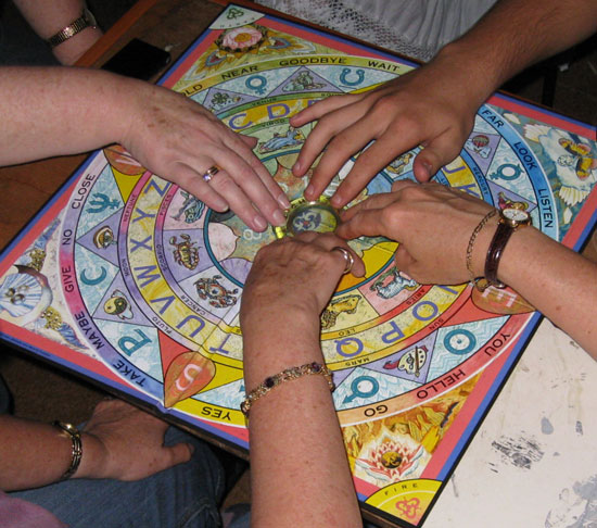 Four people using the ouija board