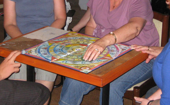 Only the medium using the ouija board, with two people holding the board to steady it.